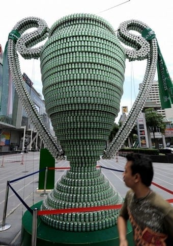 A man walks past a giant model of the UEFA Champions League trophy made of beer cans on display at a shopping mall in Bangkok on May 13, 2008.